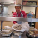 A St. Bernard volunteer unwraps some homemade cookies for the evening meal at the Catholic Multicultural Center.