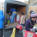 Volunteers from St. Bernard and St. Francis unload gifts from the trailer.